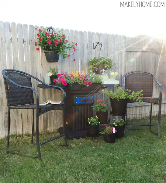 Lovely outdoor sitting area featuring a flower planter made from an upcycled BBQ grill. via MakelyHome.com