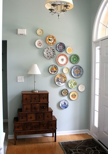 Feature wall of plates hanging in a way that gives the room some movement